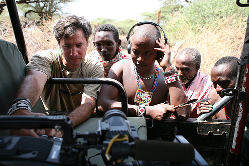 Director David Simpson shows several villagers footage in the back of his Jeep.